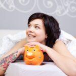 Jeune femme sur un lit avec une tirelire pour son budget matelas
