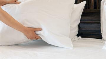 une femme pose des oreillers sur un lit