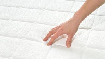 une main qui test le confort du garnissage du matelas