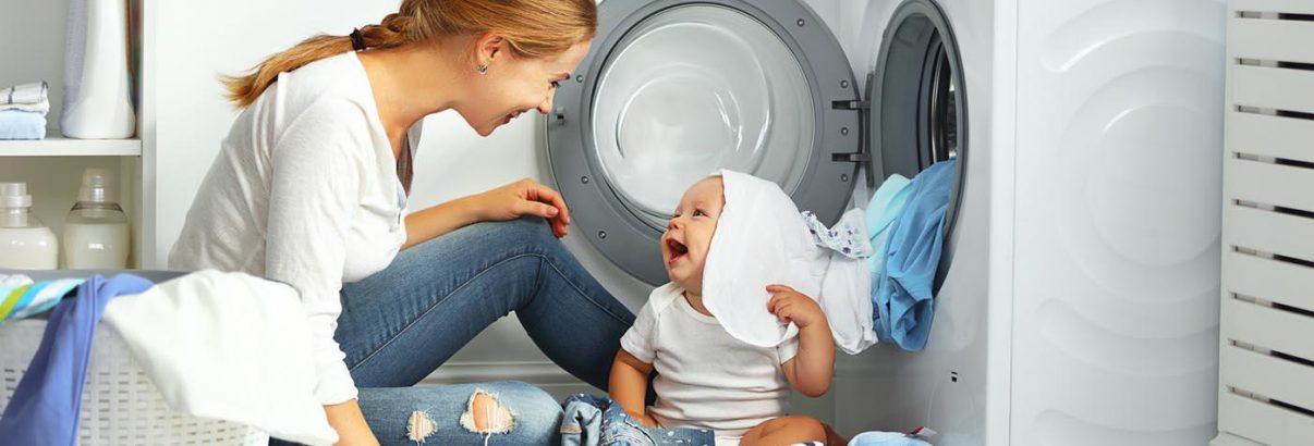 une mère à la maison lave le linge avec son bébé