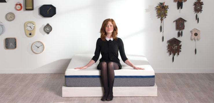 Une femme assise sur un matelas de la marque Tediber